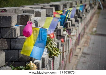 Memorial in Kiev, Ukraine, erected to the people killed by snipers on Heroyiv Nebesnoyi Sotni street during the Euromaidan revolution and protests on Maidan Square - Independence Square with a ukrainian flag on it