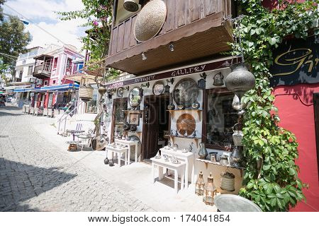 KALKAN, TURKEY - MAY 22 Storefront of antique shop decorated with shelves with antique metal trays jugs lanterns and other souvenires on cobblestone paved narrow streets of Kalkan 216