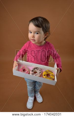 little girl  with different donuts in studio