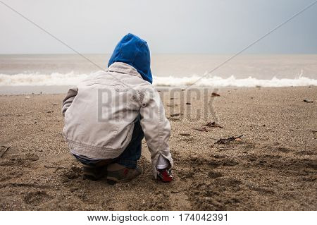 Portrait of toddler boy sitting and playing at  beach on gloomy day