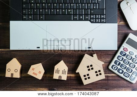 Top View Of Office Stuff With Laptop Wireless Mouse Calculator And Wooden House Toy On Wooden Table.