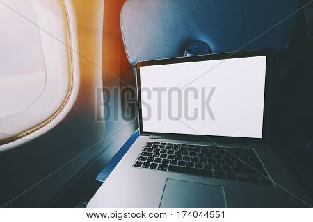 Wide angle shoot of modern laptop with blank screen on the blue table of airplane seat mock up of portable computer next to porthole of flying plane with sunny day outside