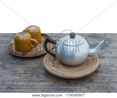 Teapot and cup on wooden table isolated