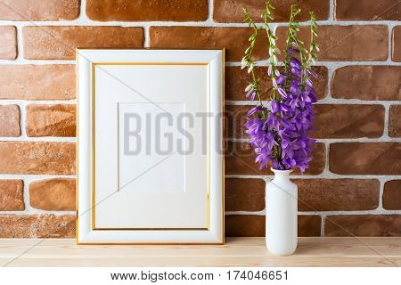Gold decorated frame mockup with bellflower bouquet in styled vase near exposed brick wall. Empty frame mock up for presentation design. Template framing for modern art.