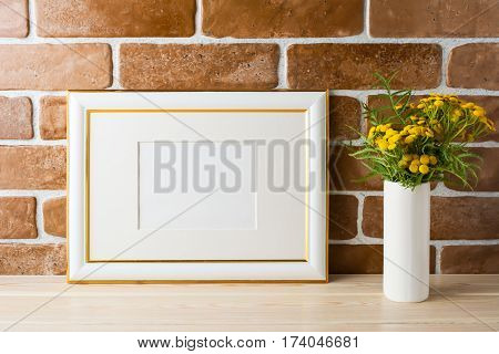 Gold decorated landscape frame mockup with wild deep rich yellow flowers in vase near exposed brick walls. Empty frame mock up for presentation design. Template framing for modern art.