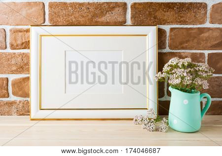 Gold decorated landscape frame mockup with wild very soft pink flowers in vase near exposed brick wall. Empty frame mock up for presentation design. Template framing for modern art.