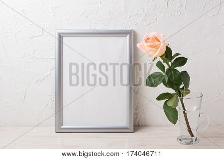 Silver frame mockup with creamy pink rose in glass vase. Empty frame mock up for presentation artwork.