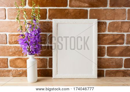 White frame mockup with purple campanula bouquet in vase near exposed brick wall. Empty frame mock up for presentation design. Template framing for modern art.