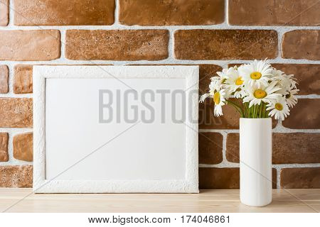 White landscape frame mockup with daisy bouquet flowers in in styled vase near exposed brick wall. Empty frame mock up for presentation design. Template framing for modern art.