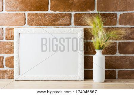 White landscape frame mockup with ornamental grass in styled vase near exposed brick wall. Empty frame mock up for presentation design. Template framing for modern art.