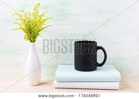 Black coffee mug mockup with ornamental green grass and books. Empty mug mock up for brand promotion.
