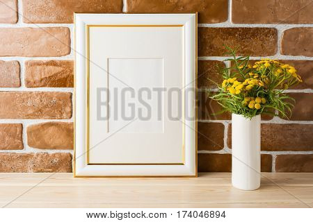 Gold decorated frame mockup with wild deep rich yellow flowers in vase near exposed brick walls. Empty frame mock up for presentation design. Template framing for modern art.