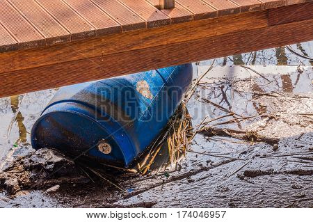 Blue plastic barrel floating in the water under a wooden pedestrian walkway at a lake in South Korea