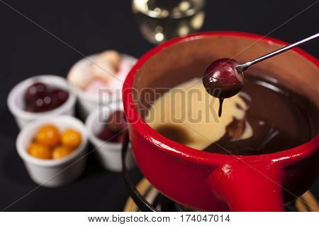 Chocolate fondue with grape on red dish