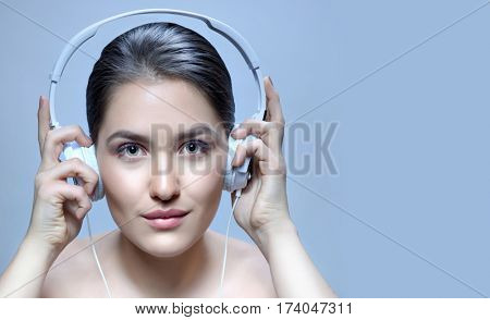 beauty closeup portrait of attractive young caucasian woman brunette on blue background studio shot lips face head and shoulders looking at camera listening music headphones