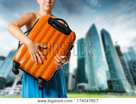 Woman In Blue Dress Holds Orange Suitcase In Hands