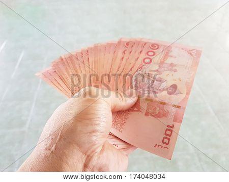 hand giving banknotes thailand, 100 baht banknotes