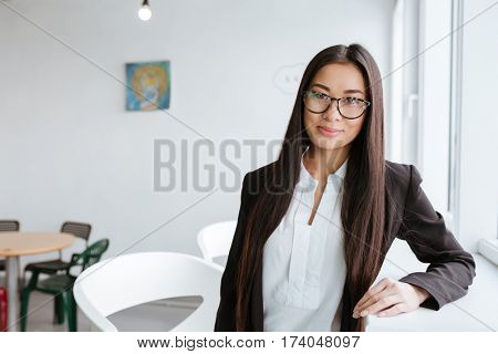 Young Asian business woman in eyeglasses and suit which standing near the window in office and looking at camera