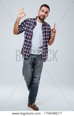 Full length portrait of Bearded man in shirt showing ok sign and pointing up while looking at camera. Isolated gray background