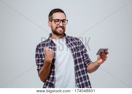 So happy Bearded man in eyeglasses with smartphone in hand. Isolated gray background