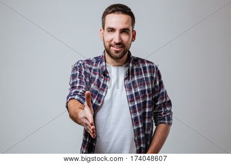 Bearded man in shirt which extends the hand at camera. Isolated gray background