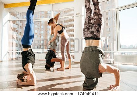 Group of people working out with instructor and doing headstand in yoga studio