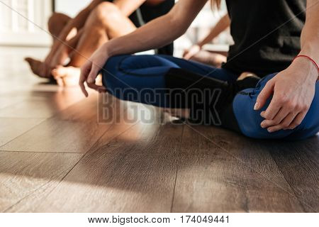 Closeup of woman sitting with legs crossed and practicing yoga in group at studio