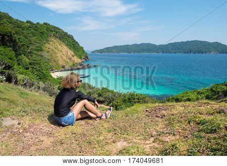 Young girl sits on a cliffThe mountains and sea scenery with blue skyIslands: Lord Loughborough Myanmar