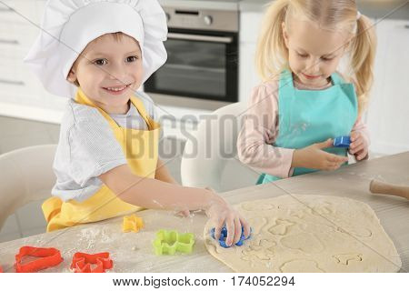 Little kids making biscuits on table