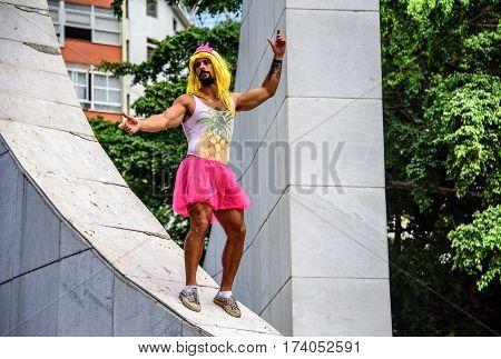 RIO DE JANEIRO, BRAZIL - FEBRUARY 28, 2017: Young man in pink crown, yellow wig, leotard and bright pink tutu skirt standing at the Memorial Getulio Vargas, Gloria neighborhood at Carnaval 2017
