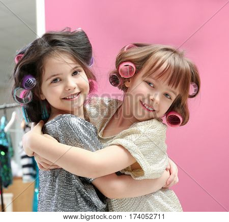 Cute little girls playing with their mother's stuff at home