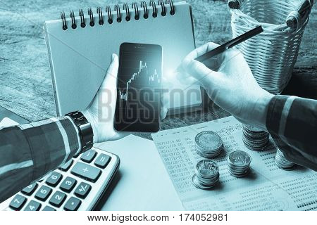 Hand in hipster shirt holding smartphone with gold coin calculator and banking account in background for finance planning concept