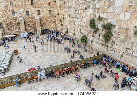 JERUSALEM, ISRAEL - MAY 23, 2016: Prayers making their wishes and prays at the Western Wall, Wailing Wall or Kotel witch is located in the Old City, view from the Mughrabi Bridge.