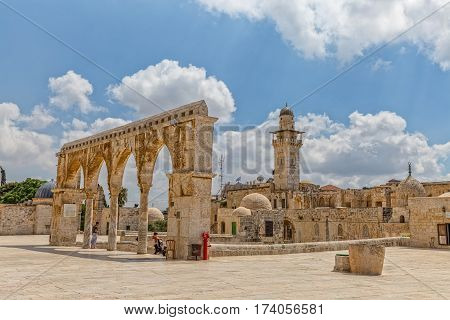 JERUSALEM, ISRAEL - MAY 23, 2016: Visitors view from the Dome of the Rock to the old stone arches at the top of the stairs and mosque minaret on the Temple Mount in the Old City.