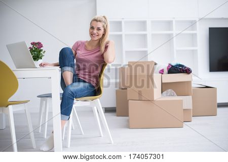 beautiful young woman moving in a new home.woman at the table using notebook laptop computer and plans with boxes around her