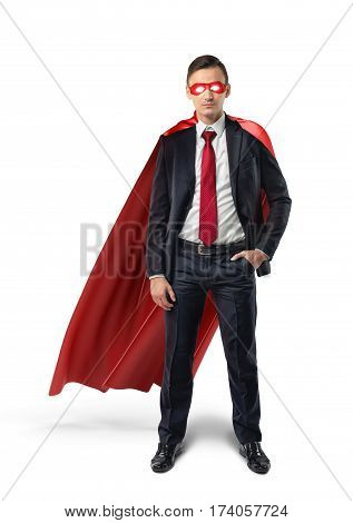 A businessman in a formal suit, a red flowing cape and a red eye mask with one hand in his pocket in front view. Business and success. Self-made people. Self-confidence.