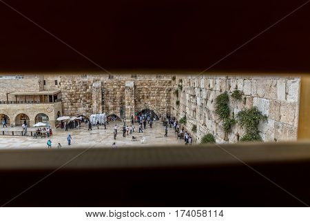 JERUSALEM, ISRAEL - MAY 23, 2016: View from the Mughrabi Bridge to the prayers making their wishes and prays at the Western Wall, located at the foot of the western side of the Temple Mount.