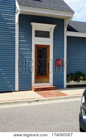 HARBOR SPRINGS, MICHIGAN / UNITED STATES - AUGUST 4, 2016: The wooden front door of a private residence on Spring Street in downtown Harbor Springs.