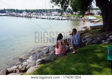 HARBOR SPRINGS, MICHIGAN / UNITED STATES - AUGUST 4, 2016: People sit on rocks along the Harbor Springs waterfront and enjoy the view of Little Traverse Bay.