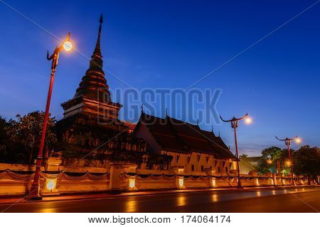 Wat Phrathat Chang Kham Worawihan in twilight scene with light trails from long exposure.