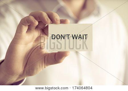 Businessman Holding Dont Wait Message Card