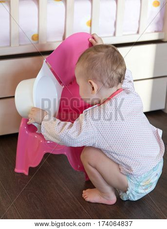 Toddler playing with baby potty . .