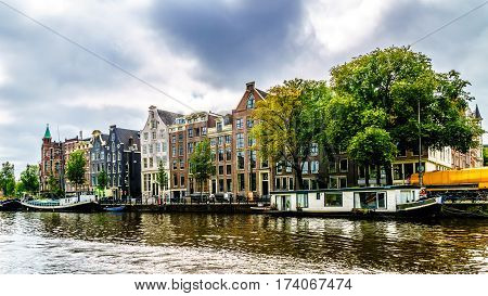 Enjoying the historic canal houses and house boats on a tour through the canals of Amsterdam, the Netherlands