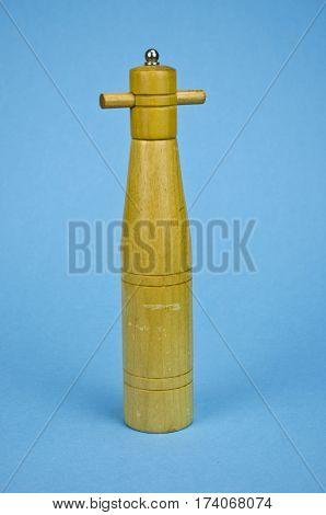 vintage wooden pepper grinder mill on blue azure background
