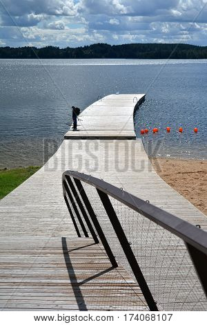 resort lake in summer with wooden bridge and fisherman