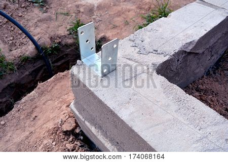 new concrete house foundation corner with anchor and trench
