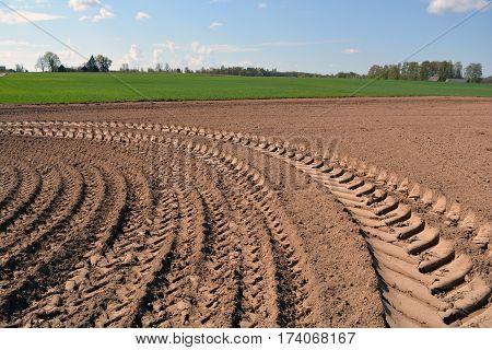 freshly plowed summer end farmland field with tractor tracks