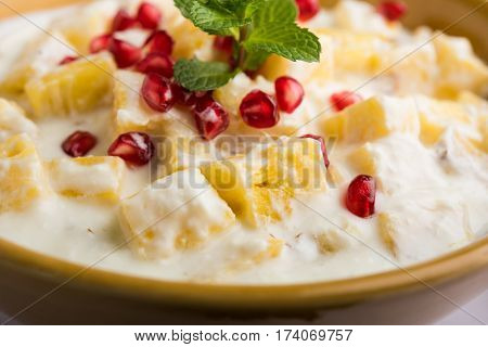 ananas or anaanaas or pineapple raita, chopped pieces of pineapple mixed with sweet curd and garnished with pomegranate and mint, favourite side dish or starter food in India poster
