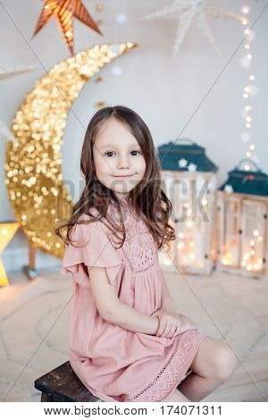 Portrait of a smiling pretty girl posing against the sparkling decoration. Christmas, birthday, party time.