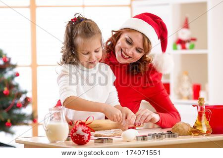 Happy child girl and mother baking x-mas cookies together at festive decorated room